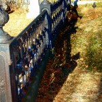 A cast iron cemetery fence in need of repair and resetting