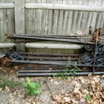 A pile of old pipe and cast iron fence parts